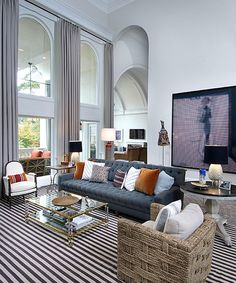 A seagrass club chair, striped floor covering and simple, silk draperies provide casual counterpoints to the grand proportions of this Atlanta sitting room by Nate Berkus.
