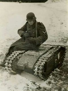 A German Wehrmacht Gefreiter with a Goliath Tank, a small vehicle controlled by remote control to destroying enemy Tanks