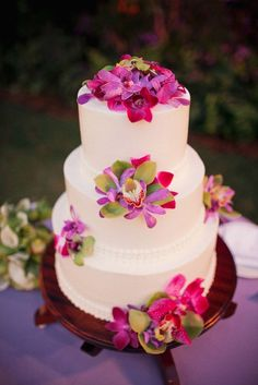White tiered cake with amazing tropical flowers