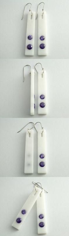 Ręcznie wykonane kolczyki z białego szkła akrylowego (pleksi) z ametystem o zabarwieniu fioletowym. Bigle zostały wykonane ze stali antyalergicznej. Długość kolczyka – 5,5cm Szerokość kolczyka – 1cm