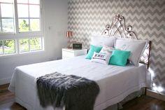 Casa Depois dos Quinze de Bruna Vieira. Cama com dossel em ferro / Papel de parede chevron / Detalhes em azul e almofadas divertidas.