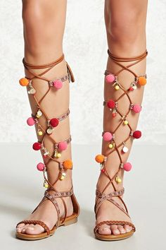 A pair of faux leather gladiator sandals featuring a caged front with geo embroidery, a lace-up front with pom pom, beads, coin trim, and tassel laces, a braided open toe, low heel, and a back zipper.