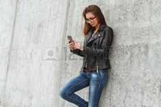 girl using mobile phone, writing SMS  on concrete wall