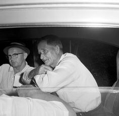 John Reyer, right, a 63-year-old local farmer,sits in the rear of an FBI car telling agents how he witnessed the abduction of Mack Charles Parker from his jail cell, in Poplarville, Miss., April 26, 1959. Reyer told them he saw four masked men throw an African-American man into the back seat of a car and drive off. Reyer had been visiting the hospital across the street. Parker was being held on the charge of raping a white woman. The trial was scheduled to start in two days. (AP…