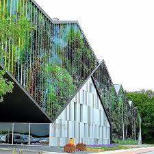 De academie door Carlos Arroyo Architecten ligt op de grens tussen de stad en het bos. De nieuwbouw versterkt de balans tussen wonen en natuur en speelt daarmee in de vormgeving. Door de dynamische gevel lijkt het gebouw voortdurend in beweging. Het optische effect zorgt ervoor dat het uitzicht verandert terwijl je wandelt. Nu eens zie je het bos, dan weer de blauwe lucht en het Westrand-gebouw.  De volumes van het nieuwe gebouw vormen een mooie overgang tussen de hoogte van de alleenstaande…