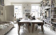 Stort spisebord og en vegg med bokhyller.