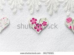 Beautiful painted wooden buttons in the shape of a heart on a spring theme on a light background with lace, can be used as greeting card, place for text. Lot of buttons on a light background