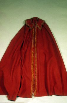 1750-1825 Red wool Shaker cape; scalloped collar & center front trimmed w/ natural linen passementerie w/ brown silk chenille; full length; no closure. Historic New England 1988.500