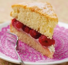A slice of victoria sponge on a pink plate with a fork