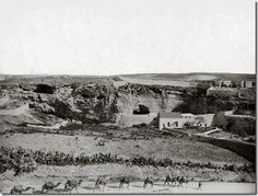 Gordon's Calvary, Jerusalem. This photo was taken between 1898 and 1914. The caves that form the eye sockets of the skull are visible just left of center.  The tomb is out of view behind the wall on the left side.  The camels are walking east along what is today a busy four-lane street.