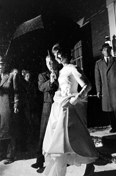 JACQUELINE KENNEDY lifts the skirt of her ivory double-faced silk satin twill inaugural ball gown, designed by Oleg Cassini, as she and PRESIDENT-ELECT JOHN F. KENNEDY leave their Georgetown home. They were en route to the pre-Inaugural Gala in Washington, D.C.  -- January 19, 1961.