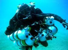 technical divers with lots of cylinders and equipment