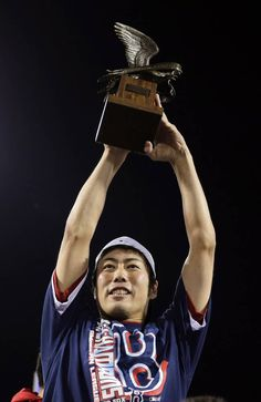 Boston Red Sox relief pitcher Koji Uehara hoists the most valuable player trophy after the Red Sox beat the Detroit Tigers 5-2 in Game 6 of the ALCS on 10.19.13 in Boston. Uehara was name the series MVP and the Red Sox advance to the World Series.