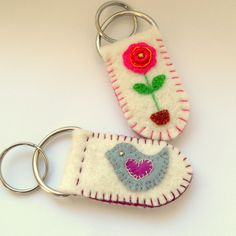 Keyrings made from felt with bird and flowerKeyring—I see them as dollhouse wall hangings!Hand stitched felt keyring -can be personalised! Beautiful hand-stitched felt keyring with either a flower or bird design. Felt Diy, Felt Crafts, Fabric Crafts, Sewing Crafts, Sewing Projects, Felt Keychain, Keychains, Penny Rugs, Bird Design