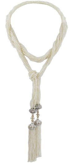 A 1920s Natural Seed Pearl Sautoir. The necklace composed of seven strands of seed pearls with openwork diamond-set beads, terminating in two tassels with a total of 32 strands of seed pearls with diamond caps. 80 old miner cut diamonds weighing approximately 1.25 carats.