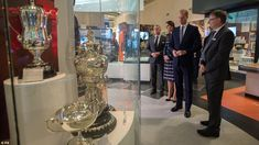 The royals examine silver ware on the display at the National Football Museum. But William...