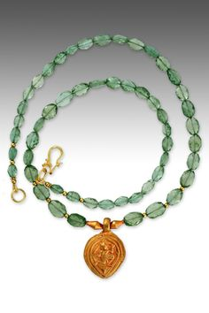 "An antique 20K-22K antique Indian plaque amulet, with a primitive rendition of Shakti - goddess of the life force on the front - and a very interesting story on the back. On graduated faceted semi-transparent grassy green apatite ovals. 18K safety clasp. Pendant drop 1"". #elleschroeder #jewelry #necklace #indian #antique #amulet #18K #22K #oneofakind #antiquesplendor #apatite"