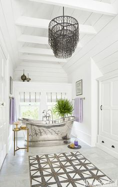 """Originally the owners were going to add a master suite, but then they looked up and realized that the third-floor attic, with its peaked roof and exposed beams, presented an unusual opportunity. """"The first thing we shopped for was that tub,"""" says Chicago-based designer Julia Buckingham. """"It's the crown jewel."""""""