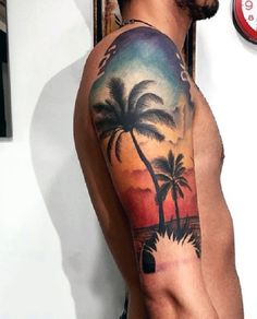 Beach tattoo on the arm with bold colors. The dark and precise colors of the tattoo help make it look striking and noticeable even from afar. The palm trees are also depicted as strong and sturdy as they stand framed by the sunset light.