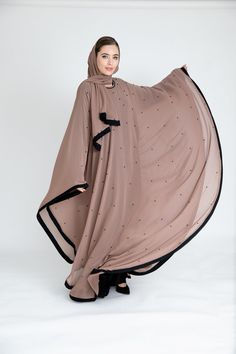 Crafted from a layer of chiffon and delicately studded with black pearls, this batwing abaya cascade into a romantic notion. Matching scarf included. Made in the UAE.