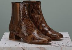 Ultra-modern but anchored in the '60s, our take on the Chelsea boot is this season's hero. Snake print uppers come with a lustrous glossy sheen while the flared heel and metallic accents are just on the right side of retro.