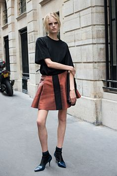 Hanne Gaby Odiele in a boxy top, pleated skirt, and heels with socks