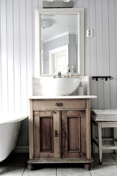 Old wooden cabinet, marble topped with bowl sink. Either a bathroom or separated toilet room.