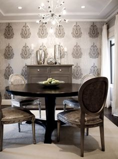 gray dining room design with gray walls paint color, Romo charcoal gray & silver two tone metallic wallpaper accent wall, Sergei chandelier pendant, mercury glass vases accents, gray painted chest buffet cabinet, gray painted ceiling, round black dining table, gray damask Louis chairs with nailhead trim, ivory rug and white silk ivory drapes.
