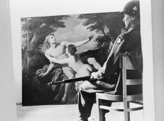 """Real Monuments Men: May 29, 1945, Germany: Pvt. Ernest Garrison of Elizabethtown, Tennessee, sits with rifle across his knees, keeps guard, and plays chaperon to """"Venus and Adonis."""" This was one of the famous paintings found among the loot stored in a cave near Berchtesgaden by Nazi leader Hermann Goering. (Image by © Bettmann/CORBIS)"""