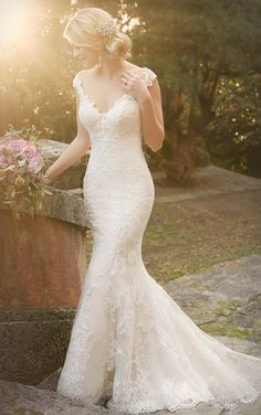 Embrace your femininity and highlight your beautiful shoulders in this stunning lace over satin bridal gown from the Essense of Australia wedding dress collection. It features an illusion tattoo lace design, scalloped hem, and a gorgeous train.