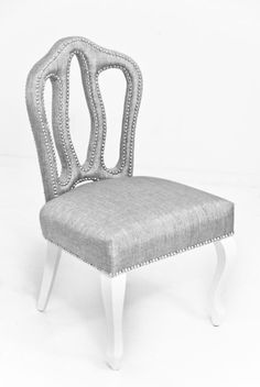 This gorgeous all over upholstered dining chair, is sculpted in the shape of a crown with a shimmery textured fabric in watson gray. The chrome nail heads bring out the beautifully shaped design of th
