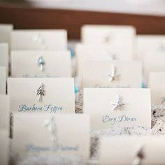 Dainty beach-themed charms decorate escort cards, adding the perfect whimsical touch to a laid-back beach wedding.
