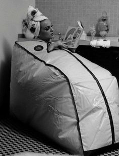 Woman reading while taking a bath in a Finnish Portable Sauna, 1962