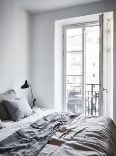 Monochrome bedroom | Grey linen sheets, black bedside lamp, balcony, glass doors | @styleminimalism