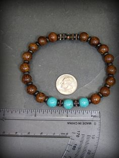 A dark earthy mens bracelet beaded in turquoise magnesite stones and dark rich Madre de Cacao Wood. Chocolate colored bone spacer beads separate with copper wheels added between the turquoise.  A great southwest rustic style for men or ladies as well. Turquoise and dark brown were born to go together... such a natural color combination.  Choose the size you will need from the drop down menu.  Look for more designs in my shop here: stoneweardesigns.etsy.com