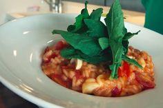 Risoto de Tomate com Mussarela de Búfala e Rúcula  1 ½ litro de caldo de legumes    100 g de manteiga sem sal gelada    1 cebola média picada    1 xícara (chá) de vinho branco seco    2 xícaras (chá) de arroz arbóreo    60 g de queijo parmesão ralado    1 bandeja de tomate cereja    1 maço de rúcula    3 tomates bem maduros    1 colher rasa (sopa) de extrato de tomate    Sal e pimenta do reino a gosto