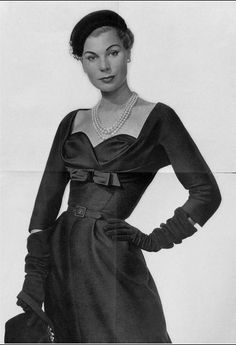 Model Stella is wearing a black silk shantung cocktail dress by Jacques Fath, 1953.