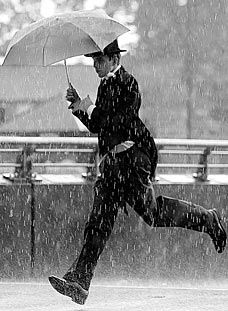 Man in suit running in rain with an umbrella