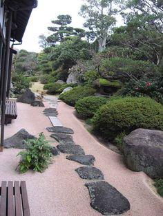 aménagement jardin japonais en pente avec du gravier décoratif, une allée en pierre naturelle et des arbustes