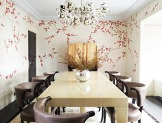 A wallpapered dining space with modern yet luxurious chairs and table