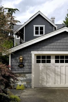 This is close to what I had envisioned for the garage! Grey shingles, white trim, good mix of stone, black accents incl. down spouts + house number. The doors will need to be CARRIAGE DOORS. #1928home #Garage #shingles  Seattle - credit: GR Home/Graciela Rutkowski Interiors
