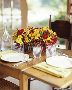 Mums are versatile blooms, as charming in casual arrangements as in considered ones. Pale-yellow 'Ginger' and orange 'Gold Strike' mums are made livelier by crimson dahlias; clusters of ruby-red rose hips gleam like jewels between the flowers. As a centerpiece, the display sets a cheerful tone for a weekend brunch.Centerpiece How-ToRose hips grow on sturdy stems that can act as a support system for the other blooms. We arranged them in a ceramic container, and nestled that inside a tin…