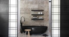 Small Bathroom with Black Freestanding Tub containing: Dark Tub Faucet with Wooden Stool also Wall Mount Shelving plus Tile Flooring together with Black And White Sliding Door