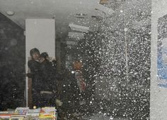 People take shelter as a ceiling collapses in a bookstore during the earthquake in Sendai, northeastern Japan, on March 11, 2011.