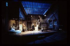 Three Days of Rain. Scenic Design by Todd Rosenthal. Line catches the eye in this scenic design because of the different placements of the element of design. The ceiling window jumps out for its vertical lines with the contrast of horizontal lines. Next, the stairwell also includes several vertical lines and a horizontal line on top. What appears to be a jai cell, also follows the same element of design with vertical lines and a contrast of horizontal lines.