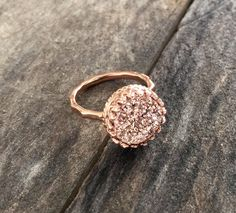 Gorgeous, rose gold druzy quartz is hand set inside an intricate rose gold vermeil crown bezel along a thin, hammered ring band. Natural, druzy gemstone is vapor coated with titanium to bring out a brilliant, consistent rose gold color. Druzy is 10mm round and unbelievably sparkly. 18K rose gold vermeil ring setting is made of sterling silver that has been heavily plated with 2 microns of pure 18K rose gold--a far more substantial layer than traditional plating. It features an intricate…