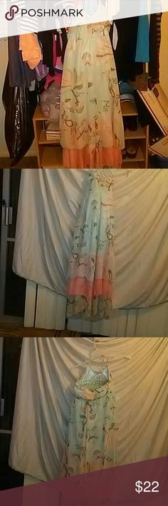 A Real Beauty backless long dress This lovely dress is one to go out on the town in. The colors are a light blue,peach, some design in brown and a gray or a tan the dress has 3 tiers the middle one is the peach color. The top covering the breast, is small V neck with truffles. And goes all around the back of the open back ties around your neck this lovely dress has never been worn. Hanging in closet. Size large material is a thin and the slip is a silk soft and it would look fab on you…