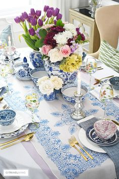 Beautiful blue and white tablescape accented with bright vibrant fresh and faux florals.