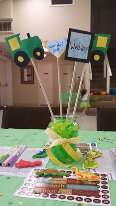 John Deere center pieces. Bouquet with paper tractors, baby's name, and due date. Water pearls used to fill the jars. Ribbon tied around the jars The paper, stickers, and markers were for a scrapbook page activity where each guest made a scrap book page for my son