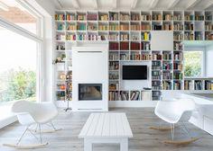 living com biblioteca, lareira e mobiliário branco